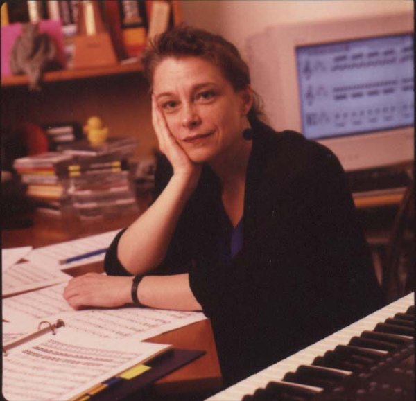 Mary Jane Leach at her work desk with manuscripts, an electric keyboard and a computer monitor in the background.