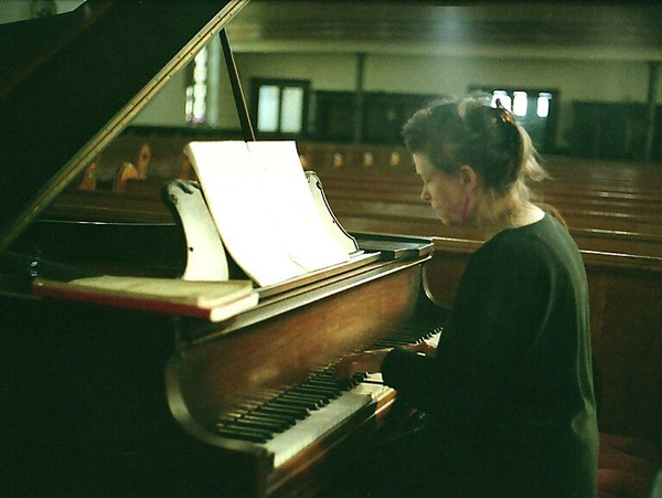 Mary Jane Leach playing a grand piano in a church.