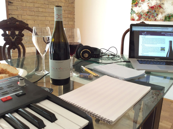 A bottle of wine and a wine glass on a tale alongside an electronic keyboard, music notation paper, headphones, and a computer screen.