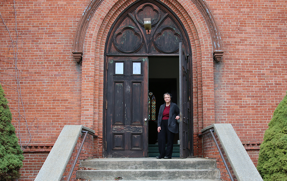 Mary Jane Leach standing outside the entrance of the church she lives in; a stained glass window is visible through the door.