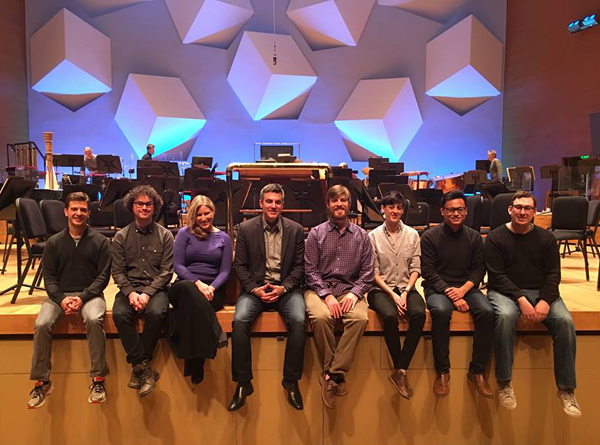Kevin Puts and the seven 2016 Minnesota Orchestra Institute Composers sitting on the edge of the orchestra stage/
