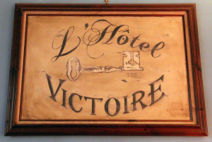 A sign for the L'Hotel Victoire.