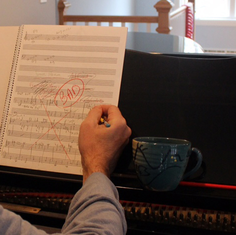 """Closeup of Jim Stephenson sitting in front of his piano, struggling in front of a piece of score paper that is marked up with various things crossed out and a section labelled """"Bad"""""""