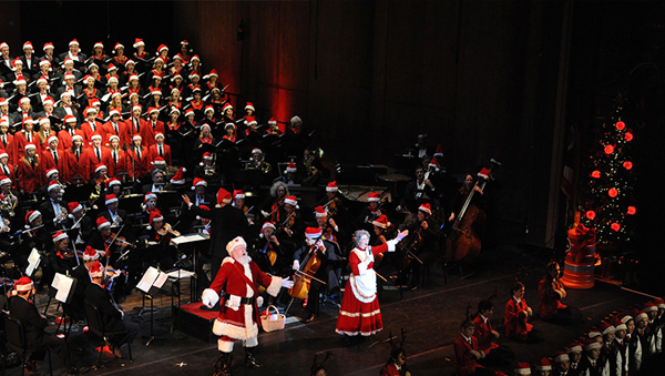 Orchestra performing with some players dressed in Santa Claus costumes.