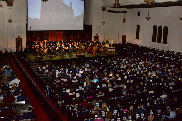 The concert at the Congregation Shaar Hashomayim showing the members of the orchestra in front of a film projection and the audience.