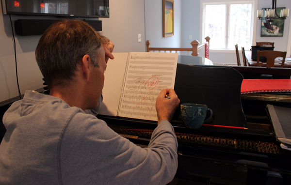 Jim Stephenson sitting in front of his piano, struggling in front of a piece of score paper that is marked up with various things crossed out and a section labelled