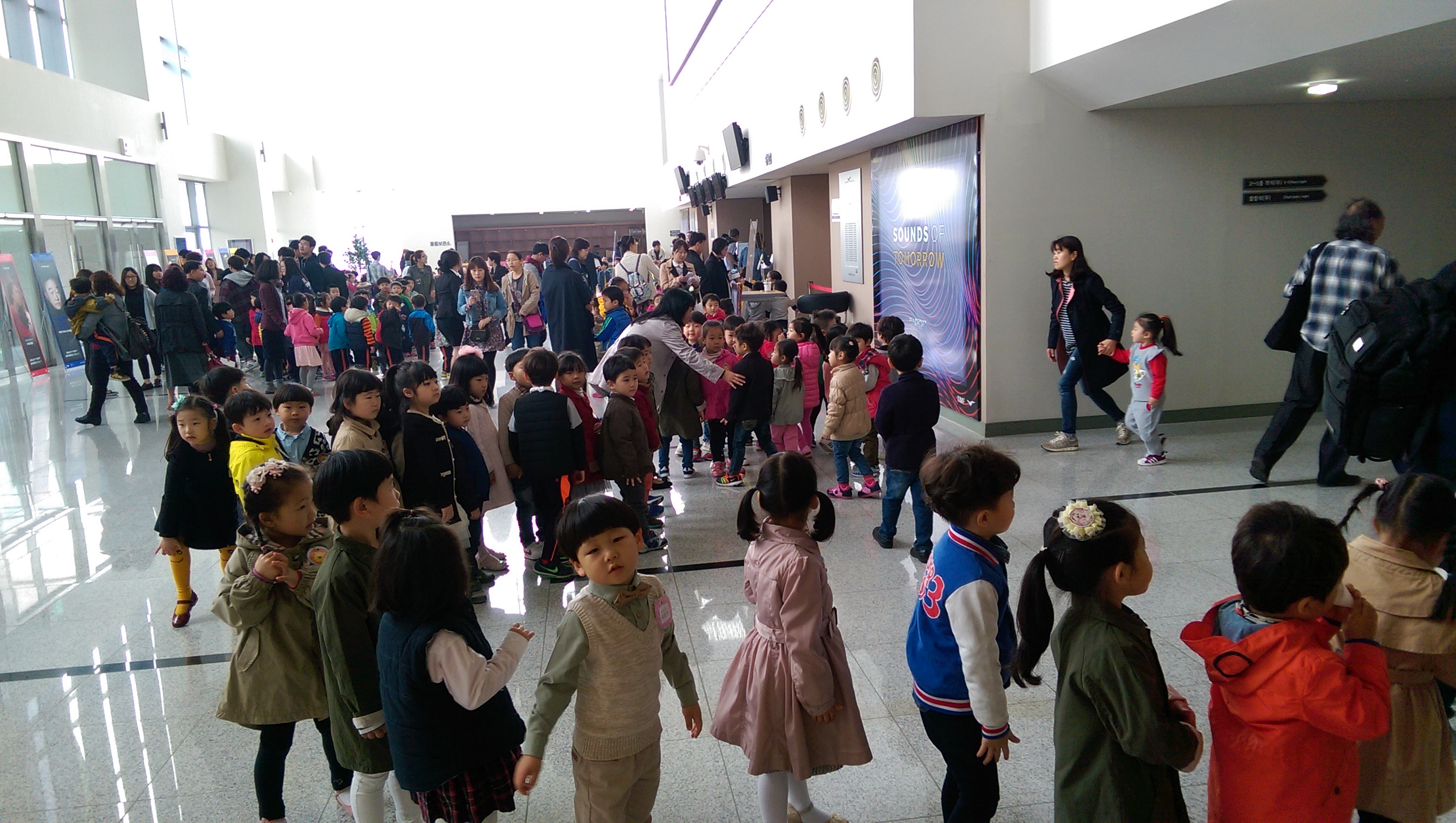 Korean children lining up inside the lobby of the TIMF Concert Hall.