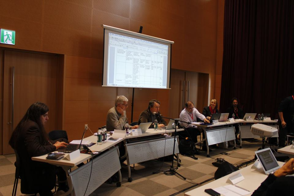 FJO seated at a series of desks along with other members of the ISCM Executive Committee, with a screen projection in back of them.