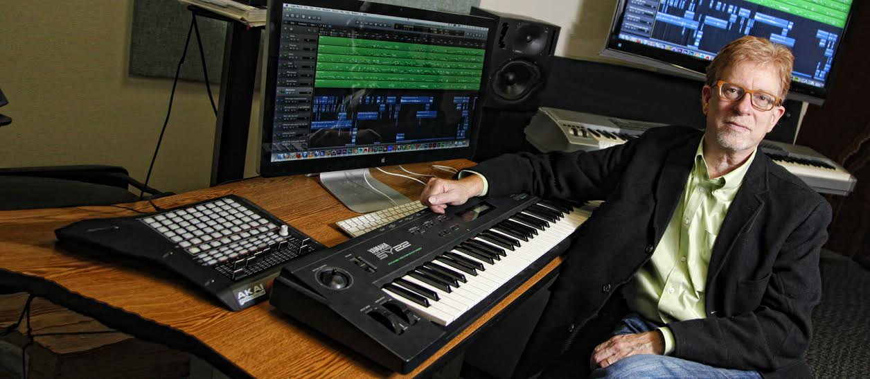 Eric Chasalow leaning on an electronic keyboard in his music studio.