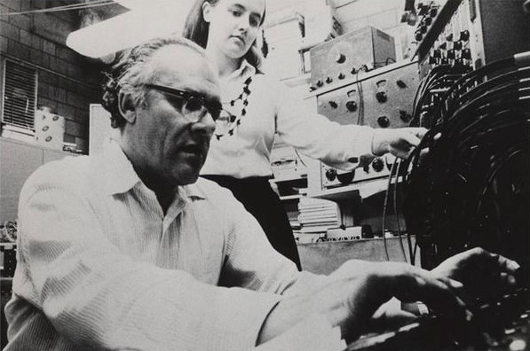 Alice Shields looks on as Ussachevsky carefully adjusts pitch settings on an analog synthesizer. In the background are three sine-squarewave oscillators.
