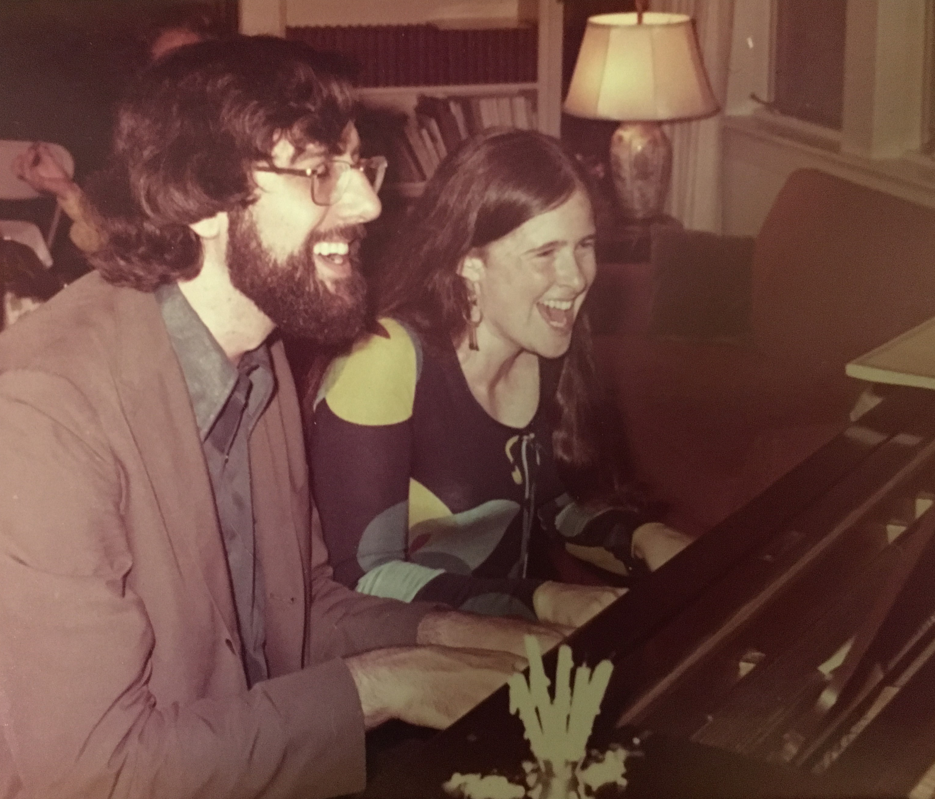 Joel Gressel and Eleanor Cory laughing while playing on a piano together.