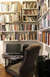 Wall to wall bookshelves surround a work station with a laptop and a chair.