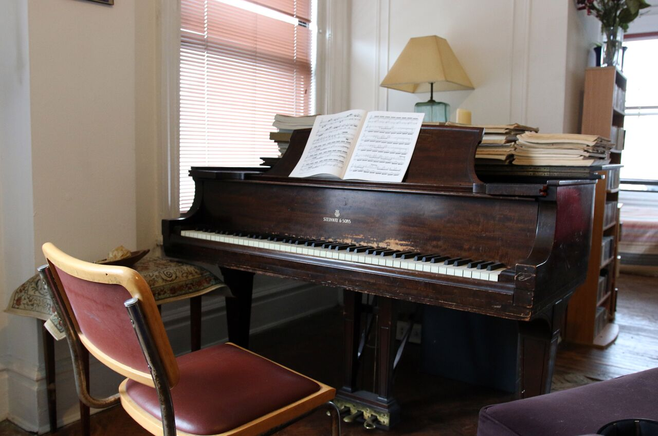 A Steinway grand piano with an open score on its music rack.
