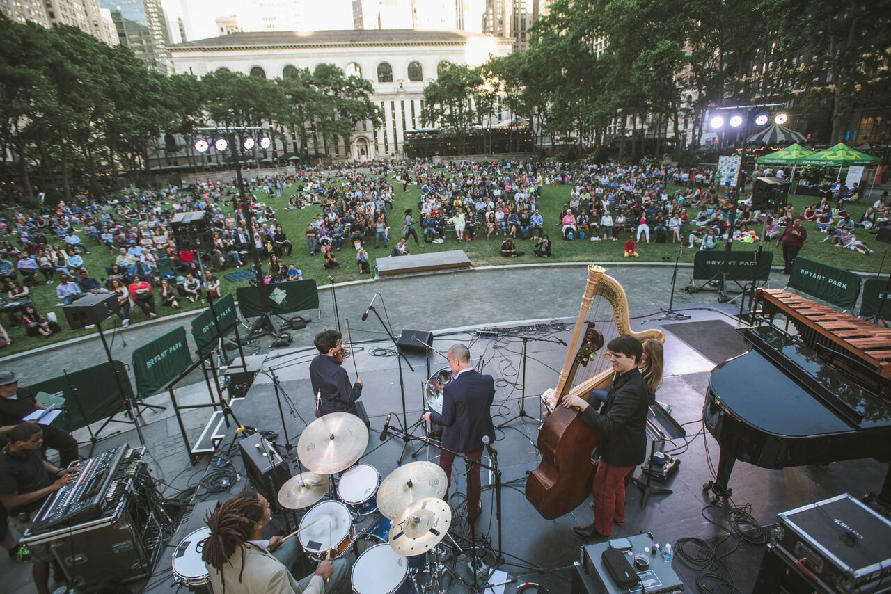 An outdoor audience listening to Andy Akiho performing on steel pans along with double bass, harp, piano, mallet percussion, and drums in Bryant Park (Photo by Ryan Muir, courtesy Bryant Park Corporation)