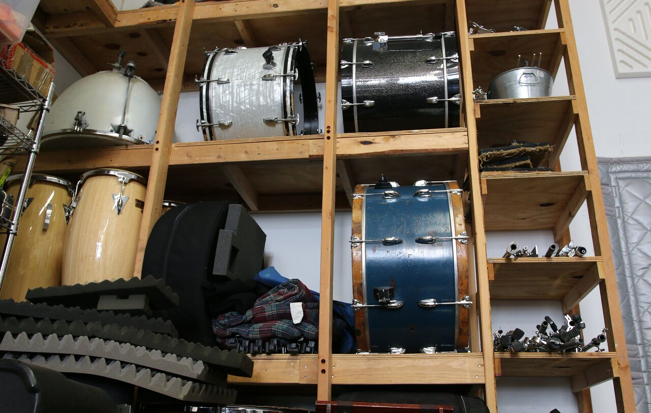 shelves of drums containing a timpano (upside down), three side drums, a pair of congas, and various drum stands.