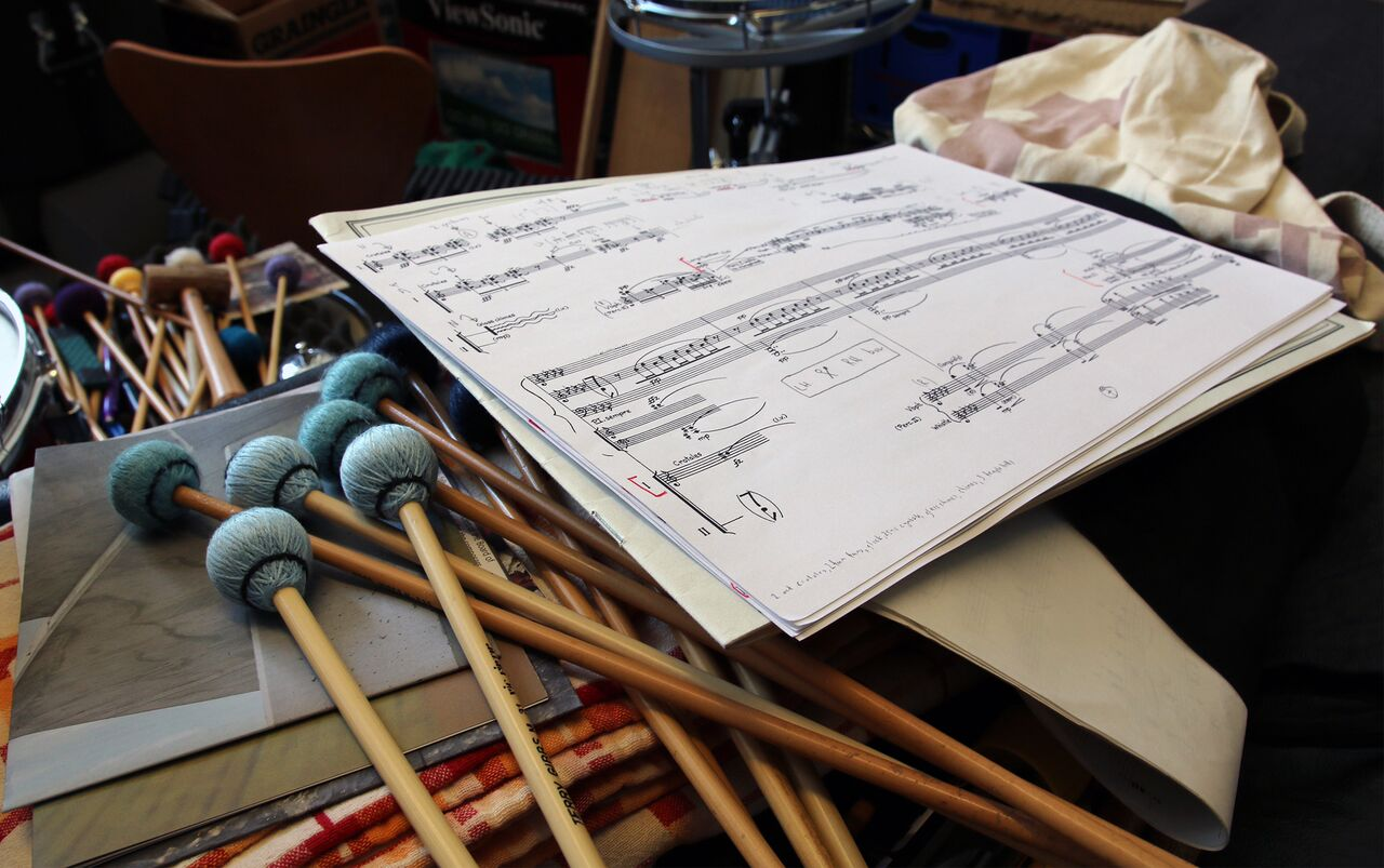 A bunch of mallets next to a page from a score.
