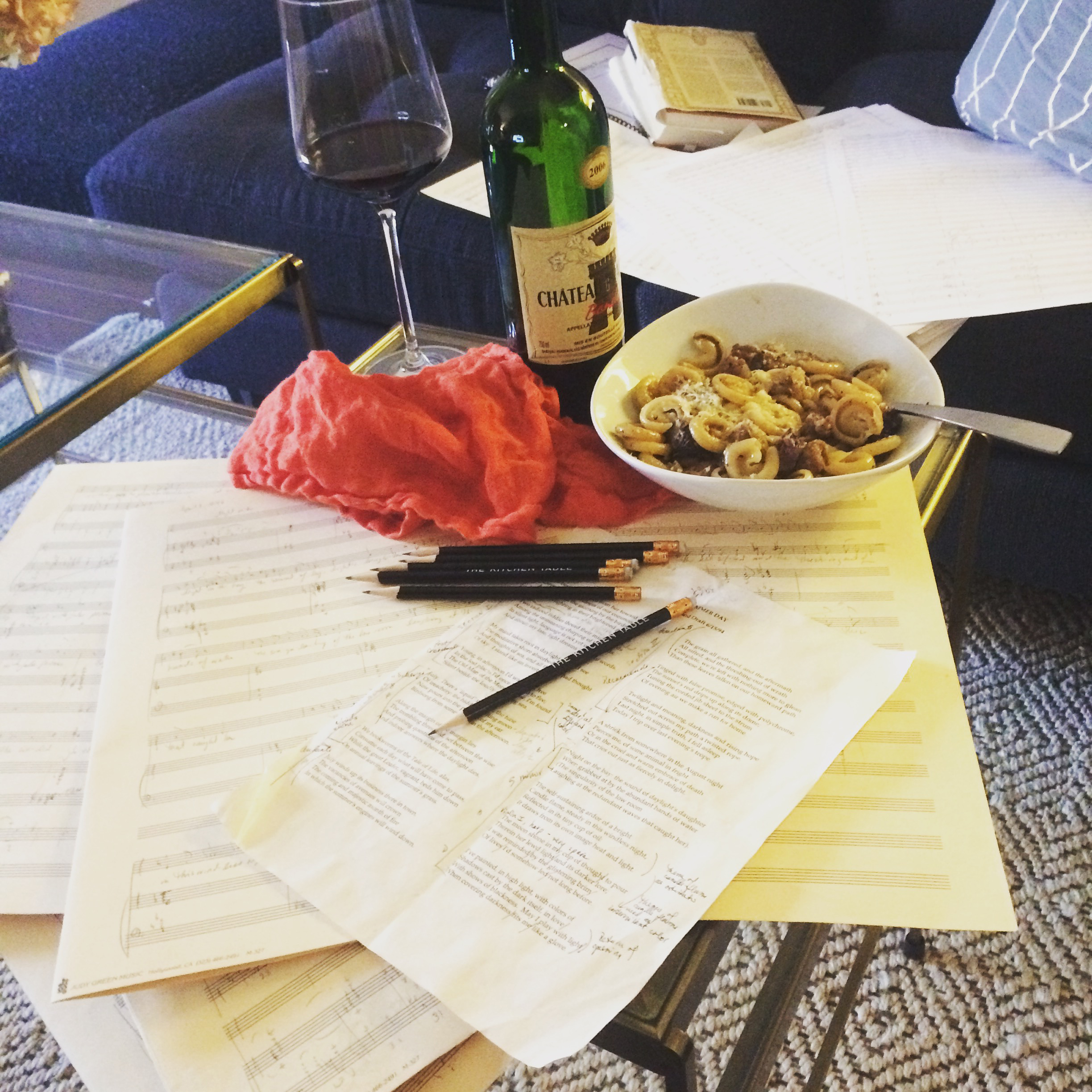 A table with pages of score manuscript paper, pens, a glass of red wine, a wine bottle, and a bowl of pasta