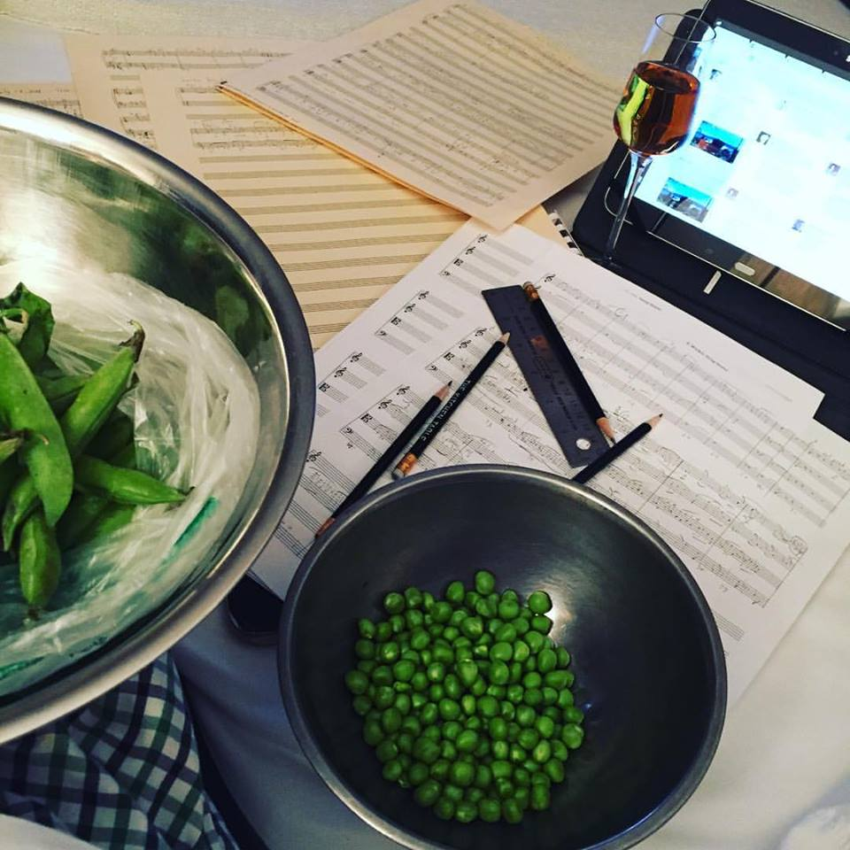 Ed Windels's table in the midst of shelling peas (with bowls of shelled and unshelled peas), writing a string quartet (with manuscript paper, ruler, and writing implements), drinking a glass of wine, and a computer monitor.