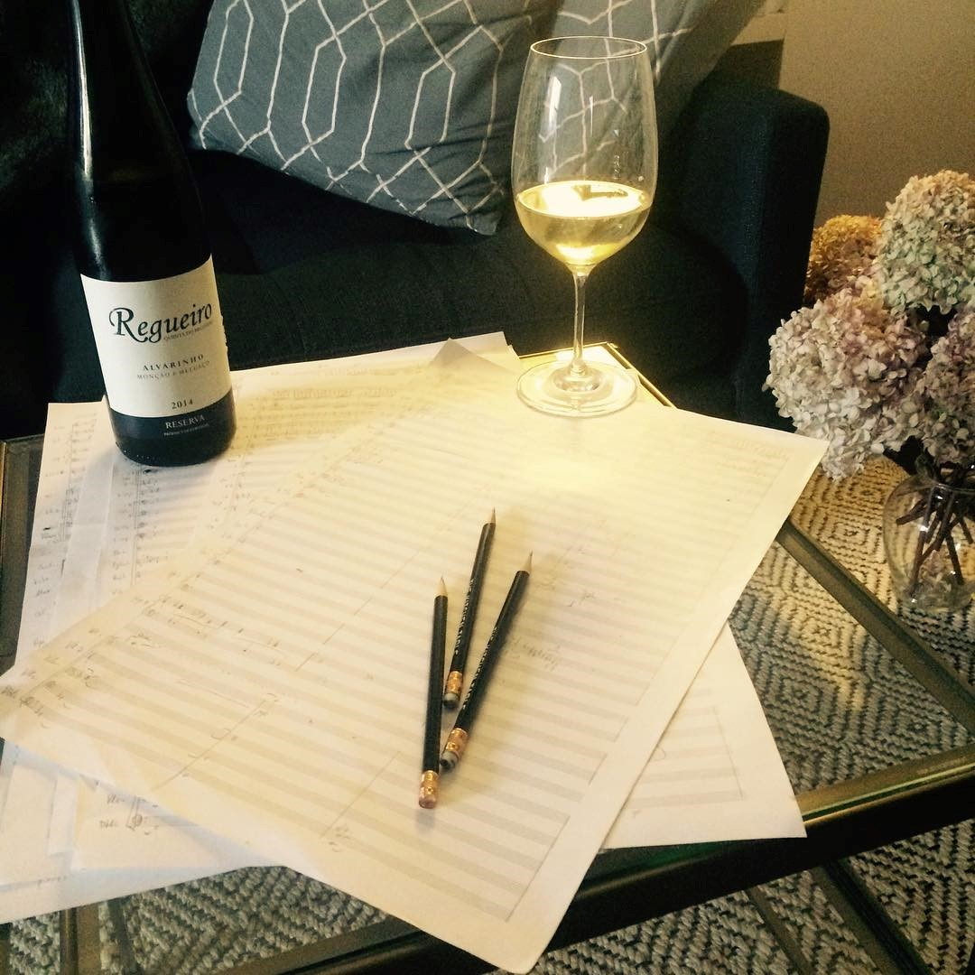 A wine bottle and a glass filled with white wine next to some page of music score paper and a few pencils.