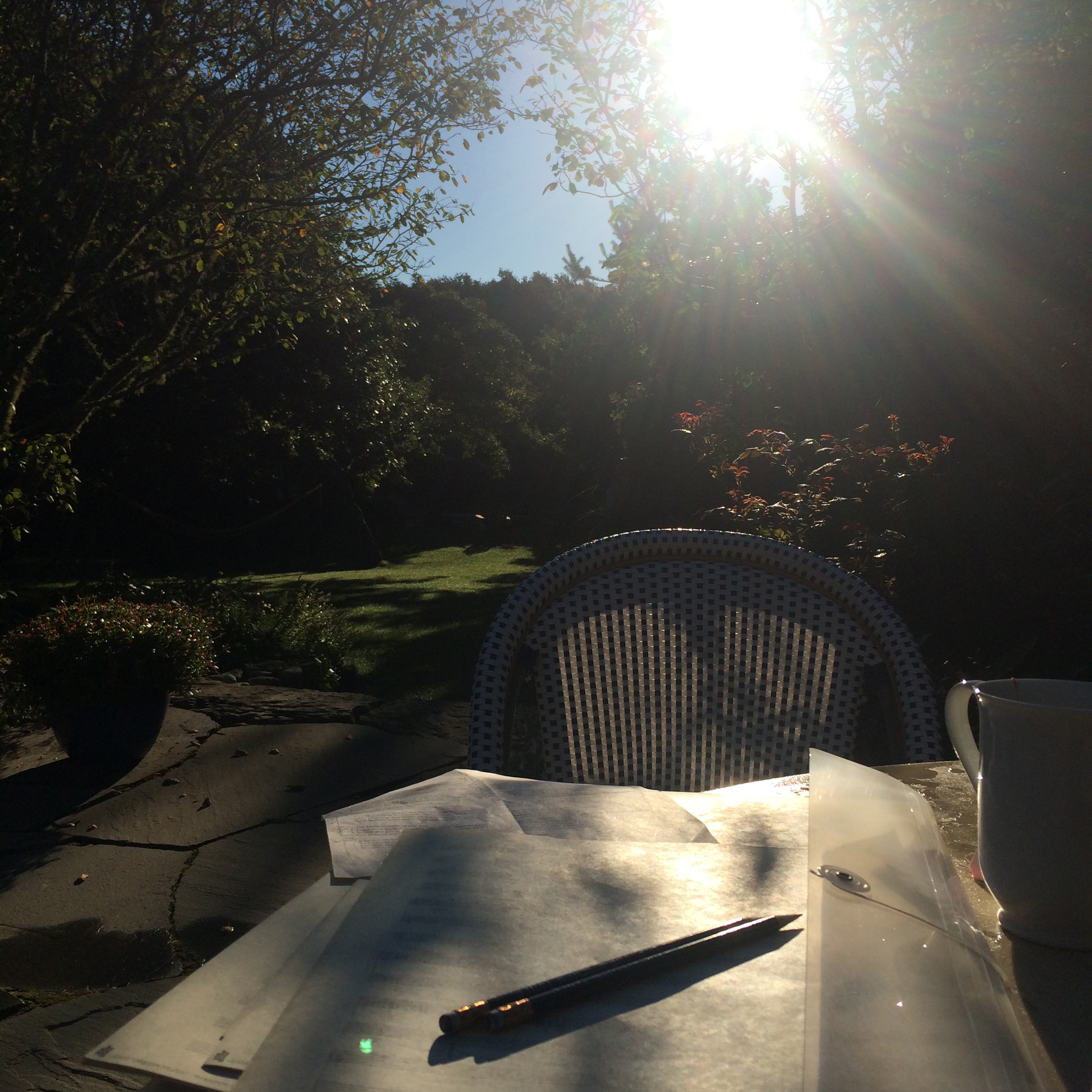 A pen sits atop a blank page of music notation paper on a table outside, the sun setting in the background.
