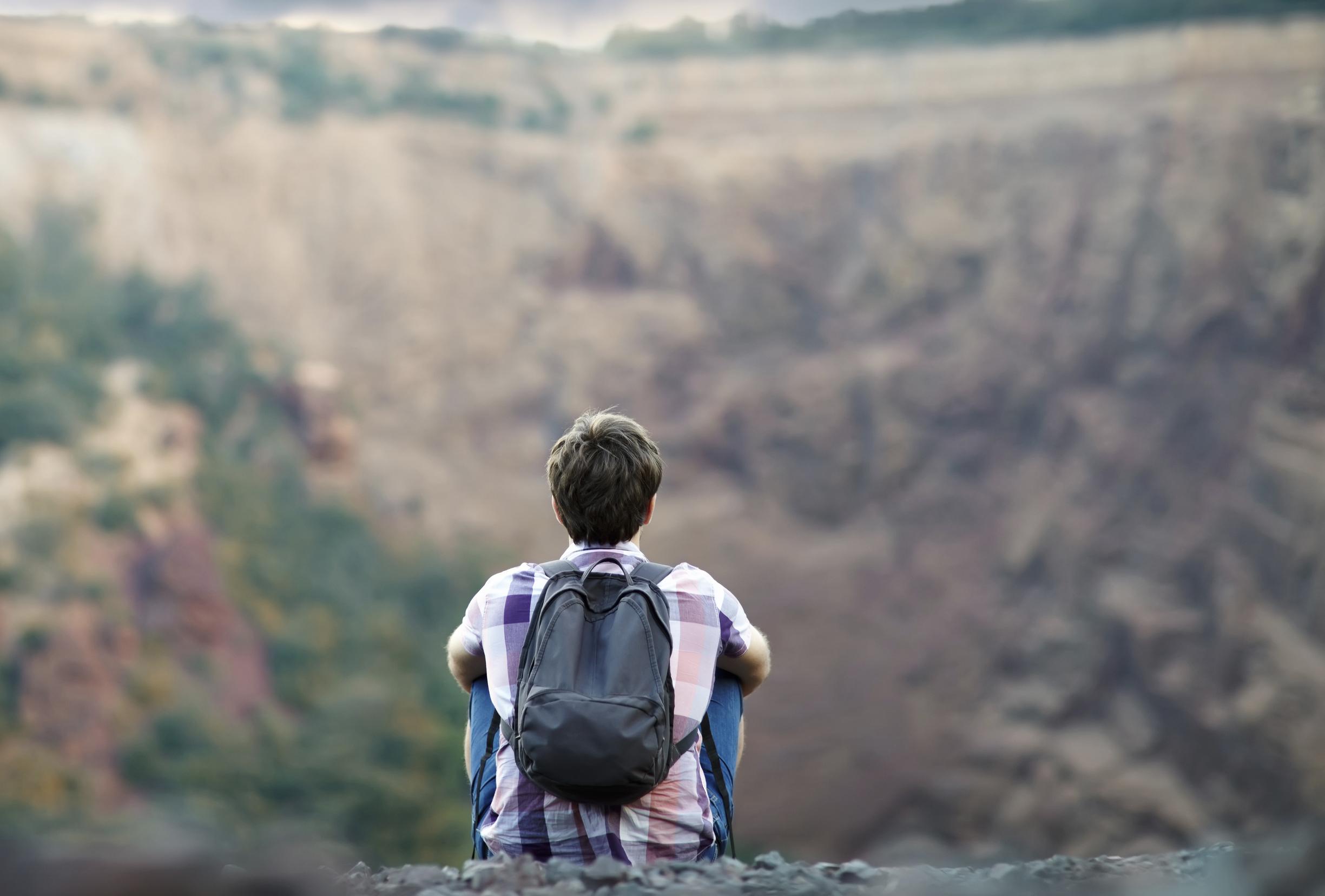 Man sitting on rocky cliff