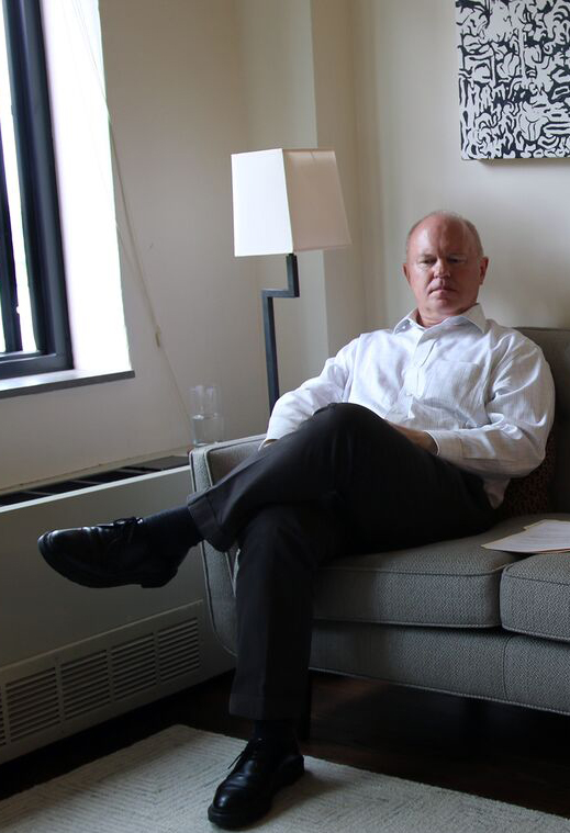Michael Torke sitting on the couch in his New York apartment.