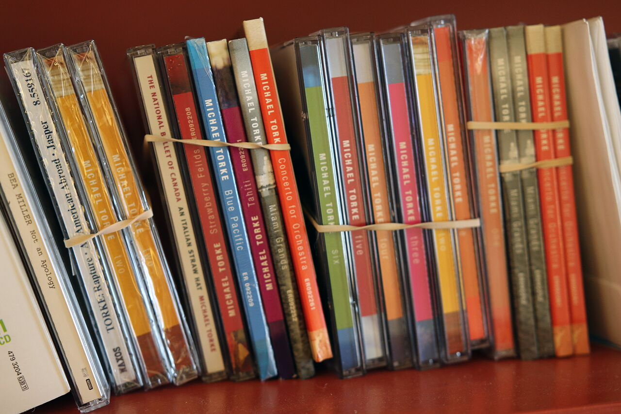 A shelf with bundles of Torke CDs grouped together with rubber bands.