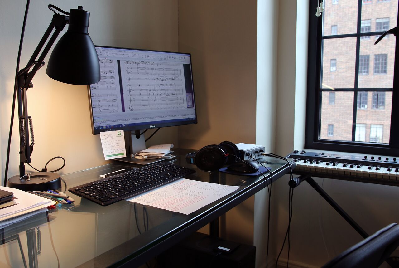 Michael Torke's spare work desk contains just a lamp, a computer with an oversized monitor; a digital piano is off to the side.
