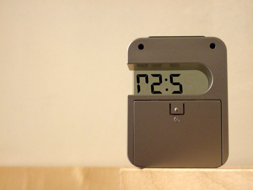 A photo of a digital time display with backwards numbers by Kenneth Lu