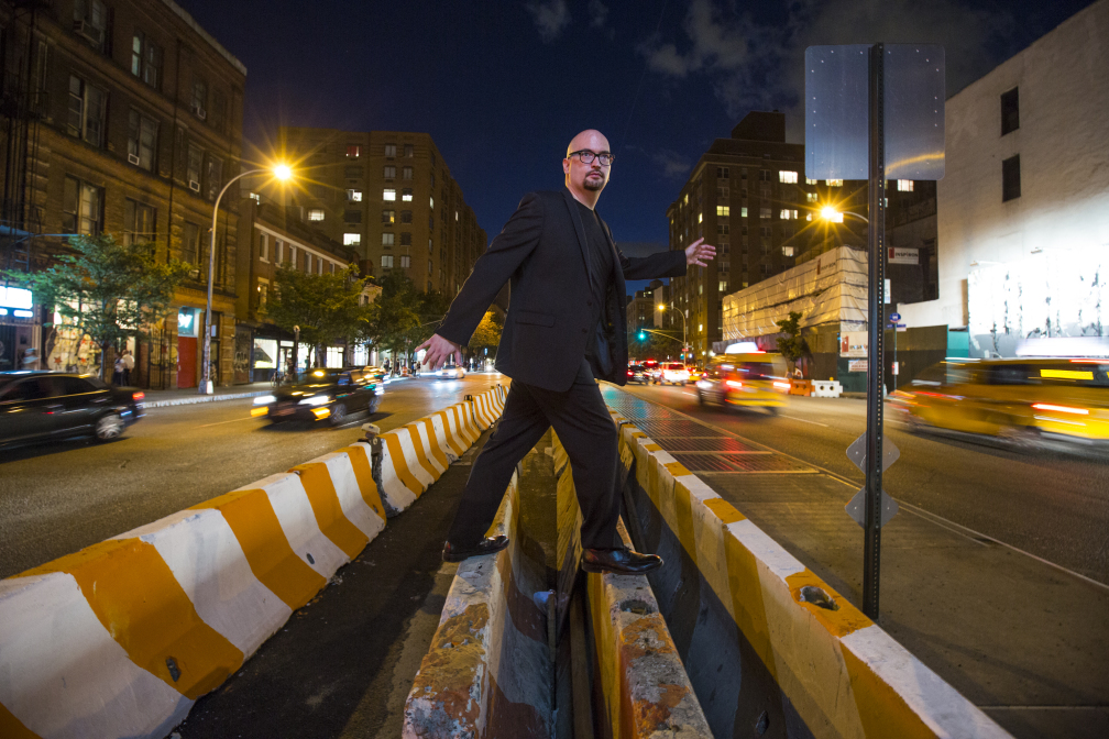 Ethan Iverson walking across a roadblock in the middle of a street. (Photo by Jimmy Katz)