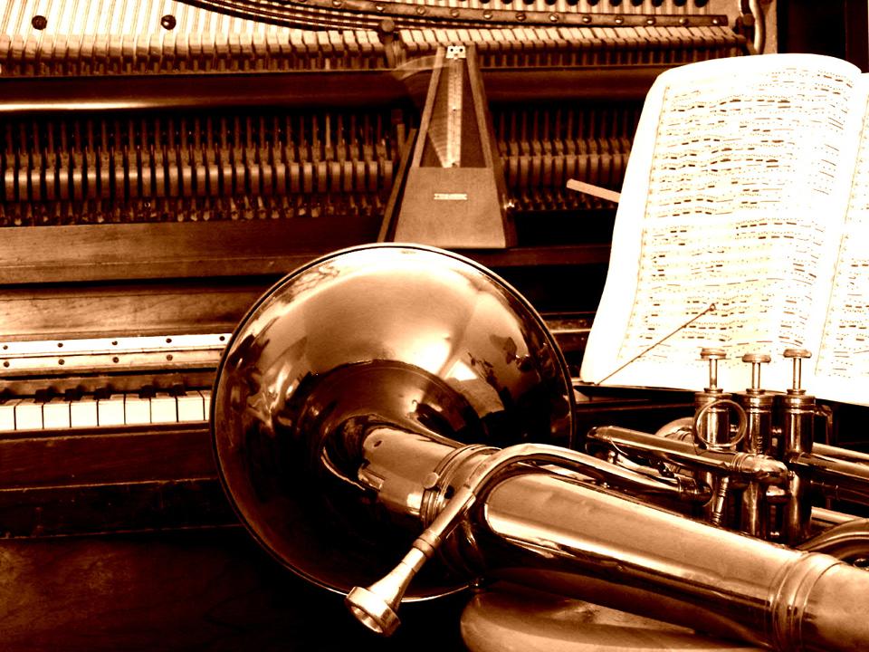 An open piano, a metronome, a tuba, and some sheet music