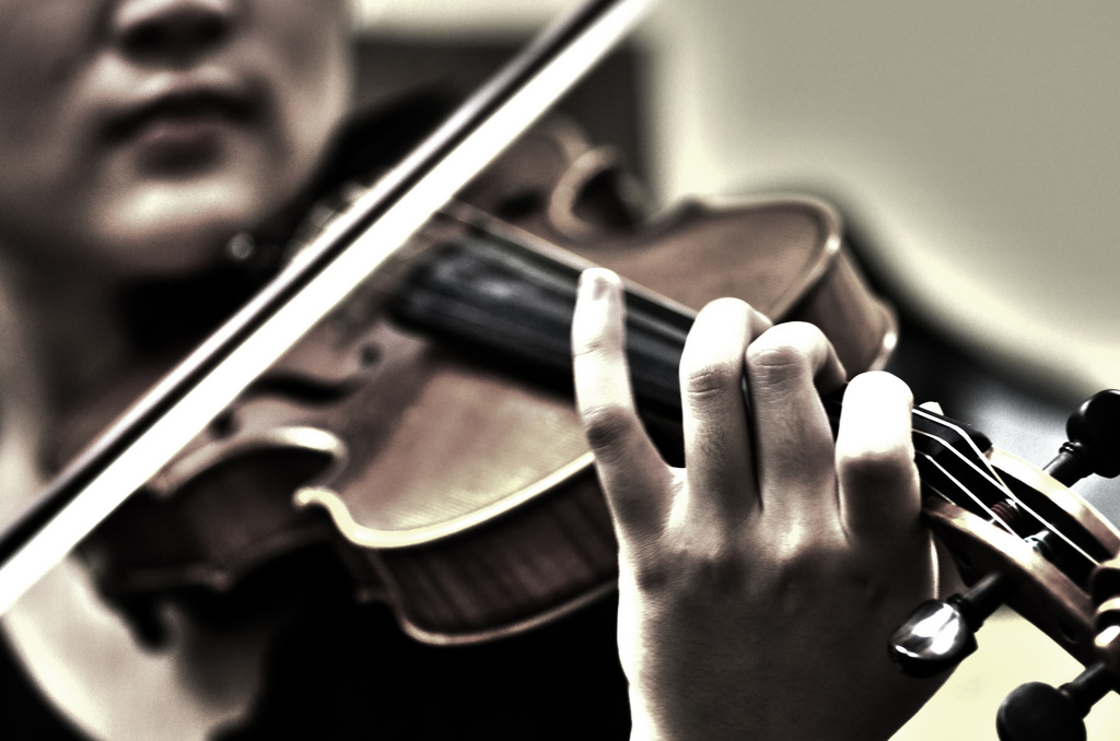 Violinist bowing on a violin in standard classical music playing position (under the chin)