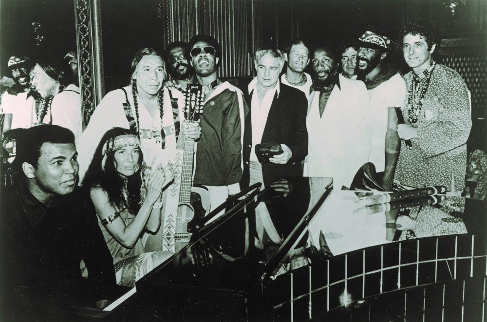 A group photo from 1978 at the end of The Longest Walk, a 3,800 mile protest March from San Francisco to Washington, D.C. Muhammed Ali sits at far left, and at the far right is David Amram. Marlon Brando is at the center, sandwiched between Stevie Wonder and Dick Gregory.