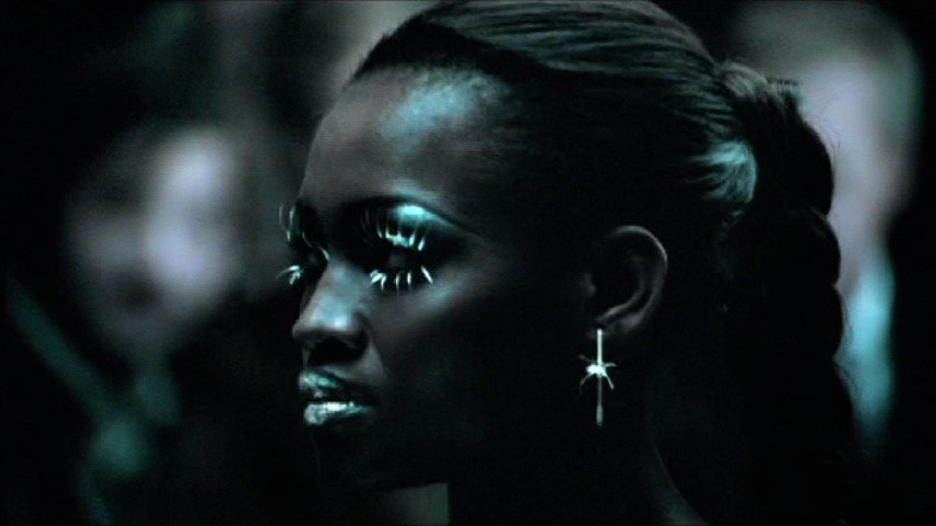 A still from the Cadillac Super Bowl ad scored by COPILOT featuring a n almost robotic-looking female model with prominent silver lipstick and eyeliner as well as a silver earring