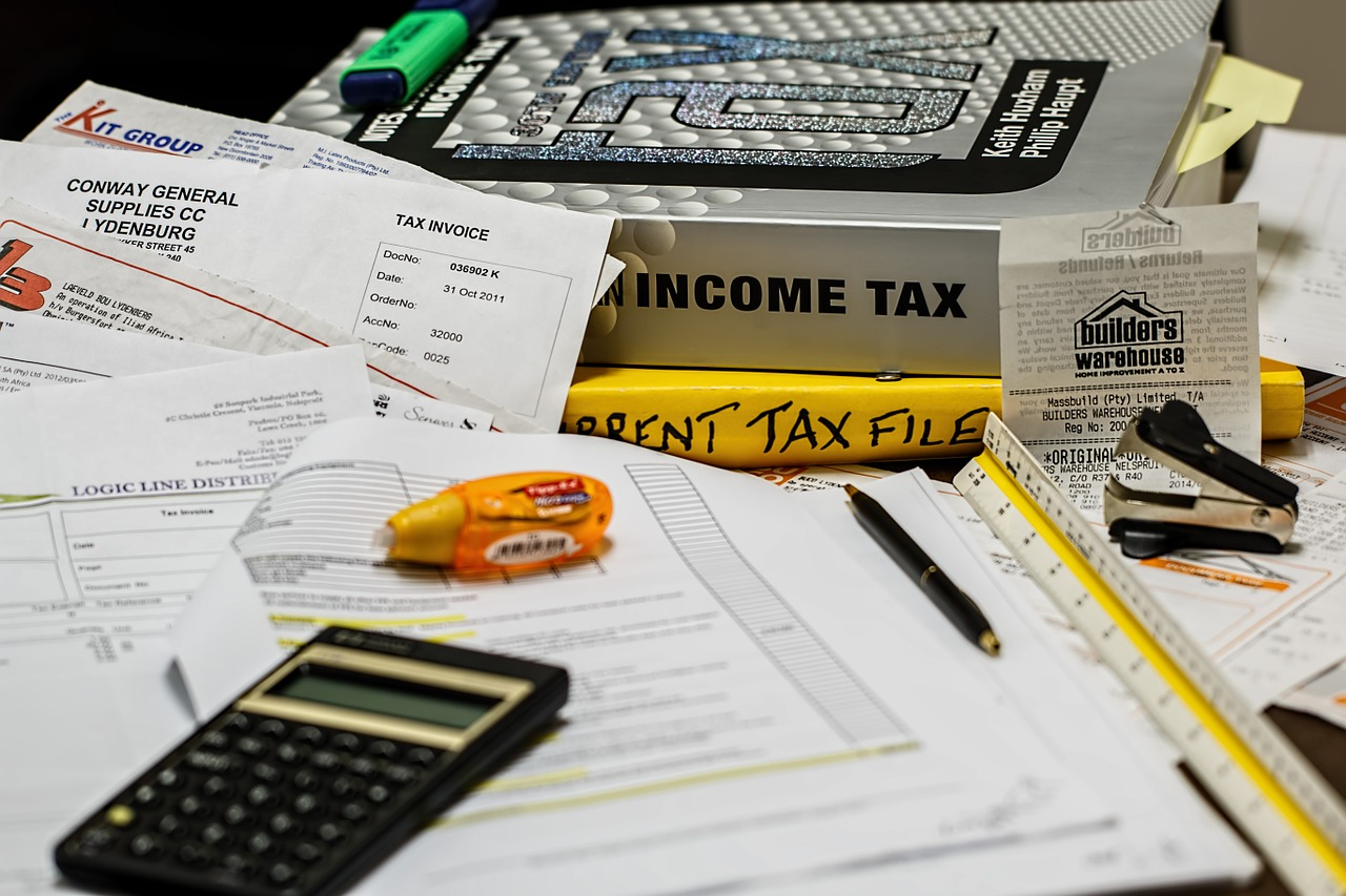 A pile of tax forms, books on tax preparation, receipts, a pen, an eraser, and a calculator