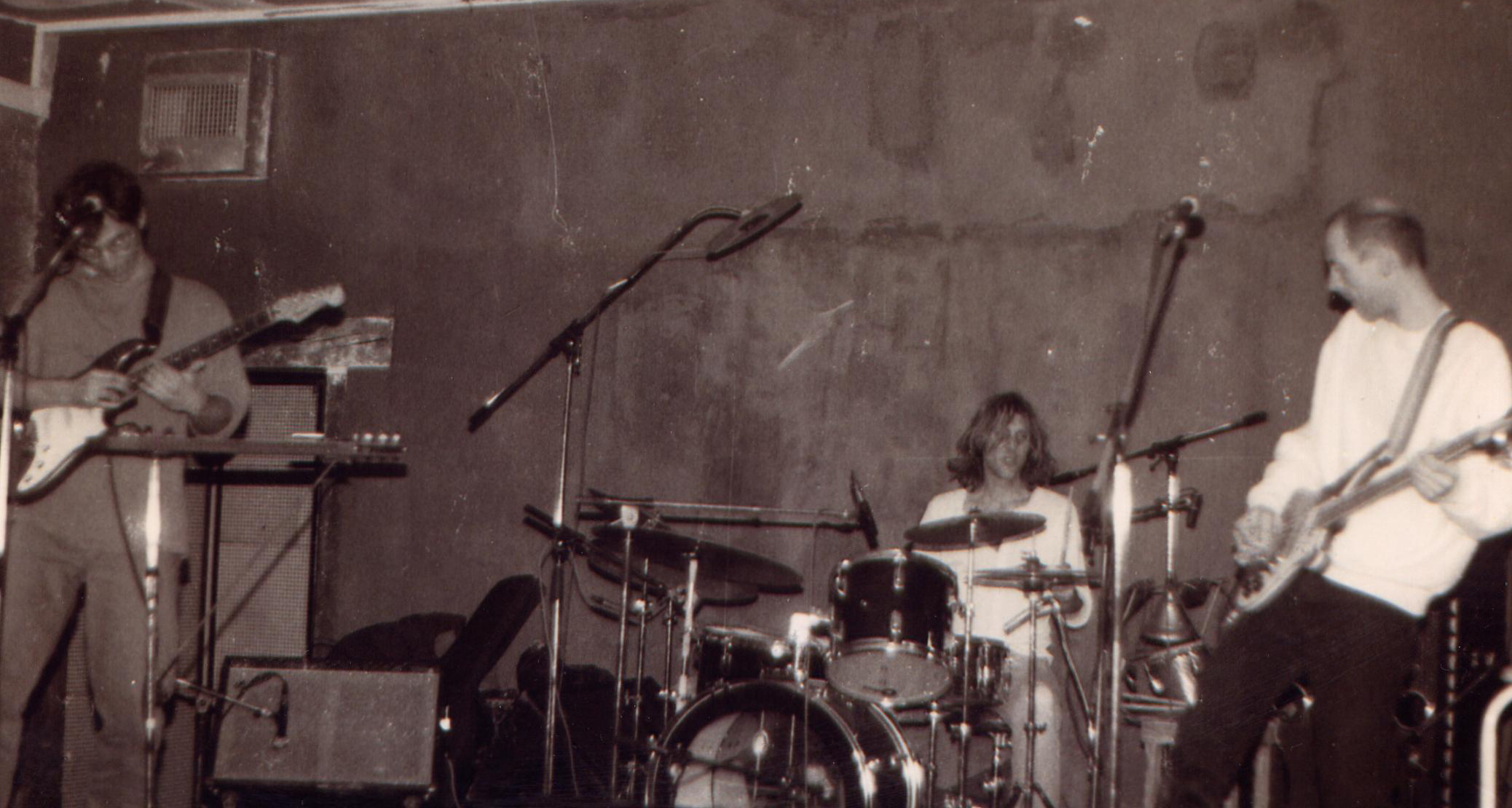 Mike Johnson playing guitar with Dave Kerman on drums and Bob Drake on bass