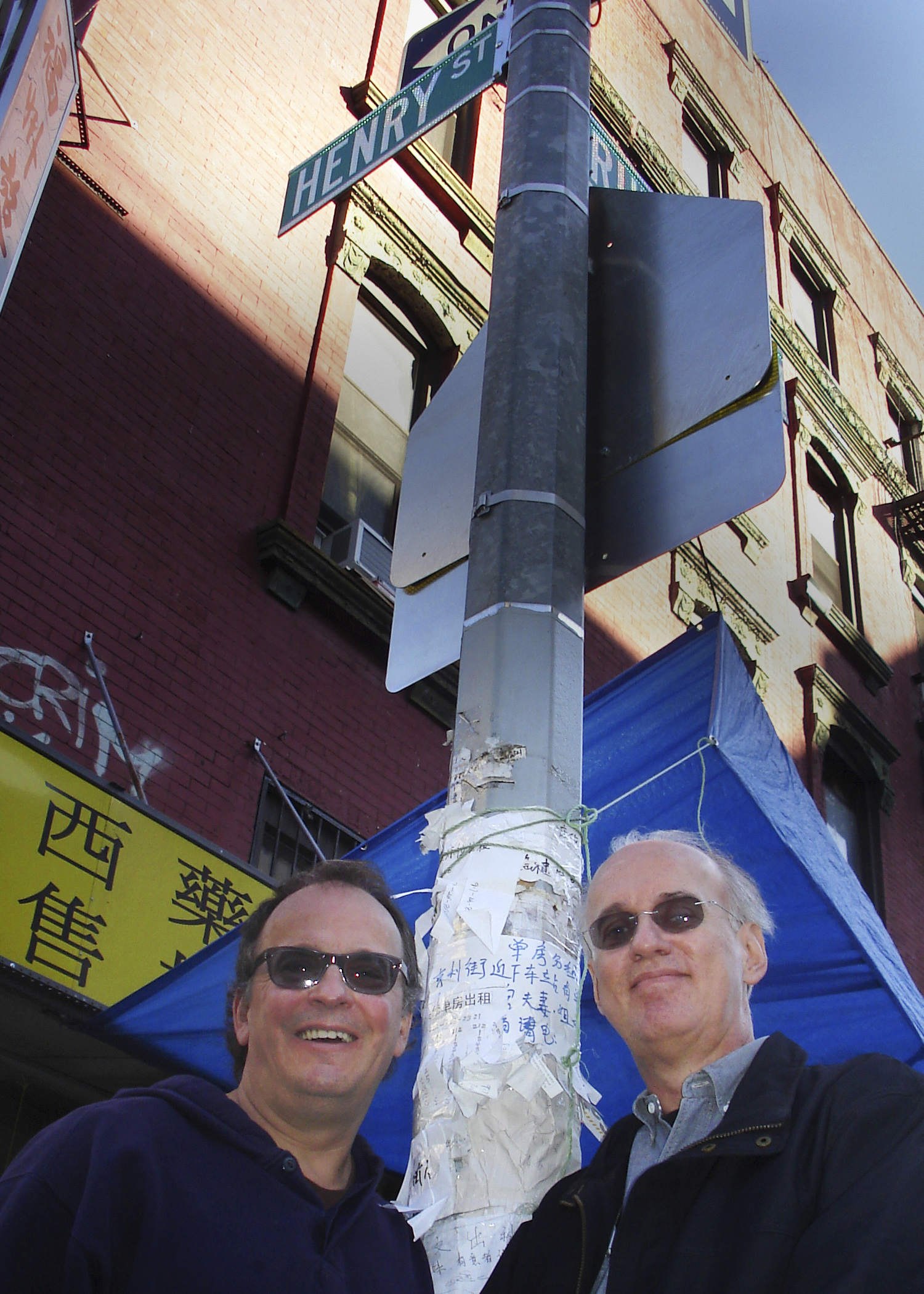 Phil Kline and Tom Steenland both wearing sunglasses and standing on opposite sides of a traffic pole on a city street corner.