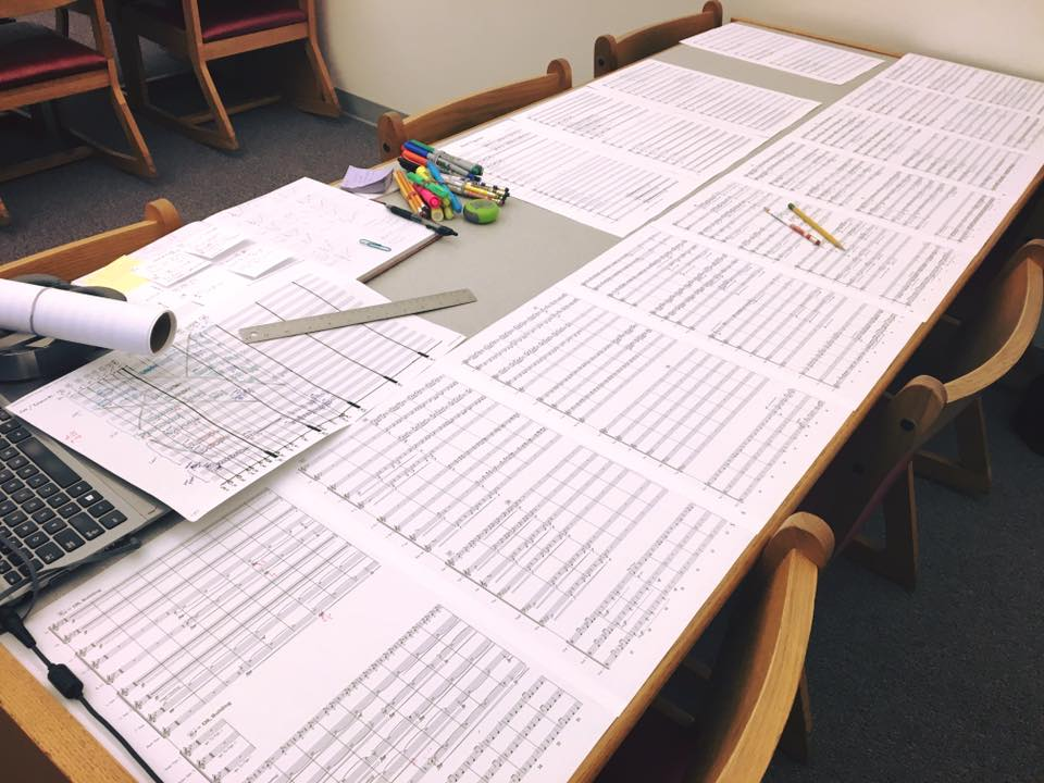 A long desk covered with pages from a musical score plus a calculator and various writing implements.