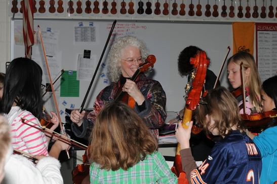 Martha Mooke demonstrating string techniques for students at a clinic.