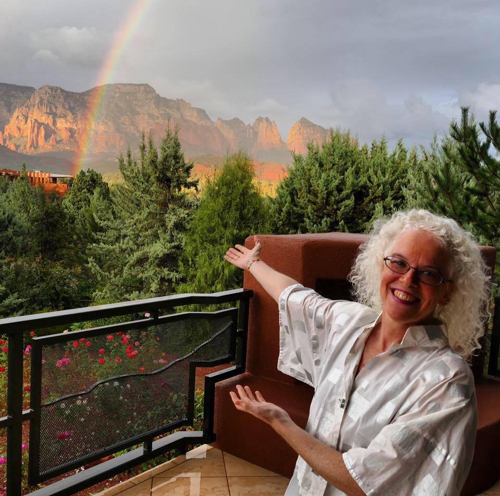 Martha Mooke outside in Sedona; thre's a rainbow in the sky.