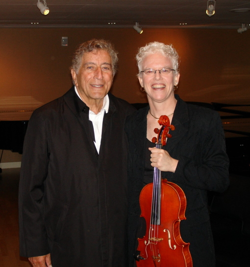 Tony Bennett standing next to Martha Mooke who is  holding a viola.