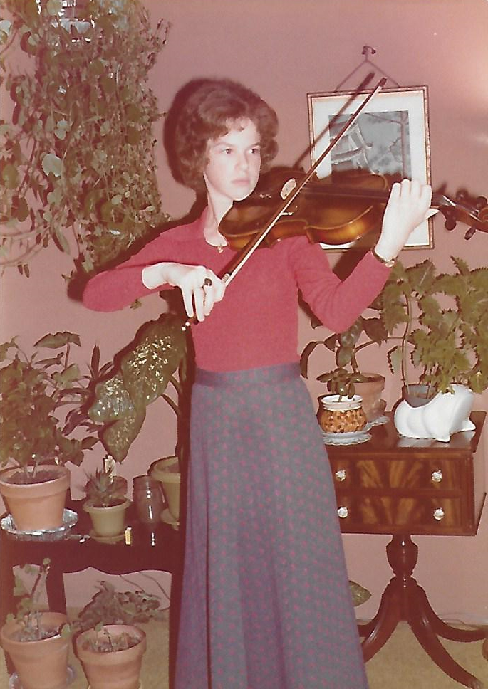A very young Martha Mooke playing viola at home in front of a bunch of potted plants.