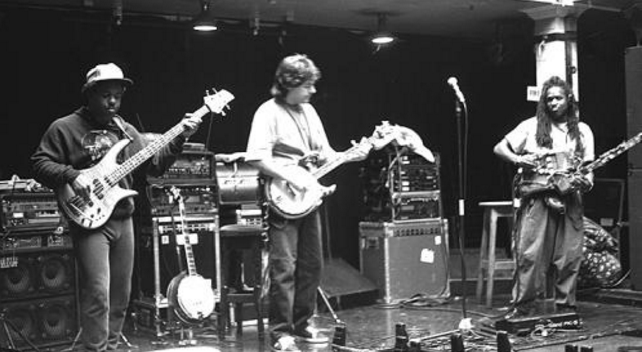 Béla Fleck (center) in performance with the Flecktones: Victor Wooten (far left, playing electric bass guitar), his Roy Wooten a.k.a. Future Man (far right, playing the Drumitar)