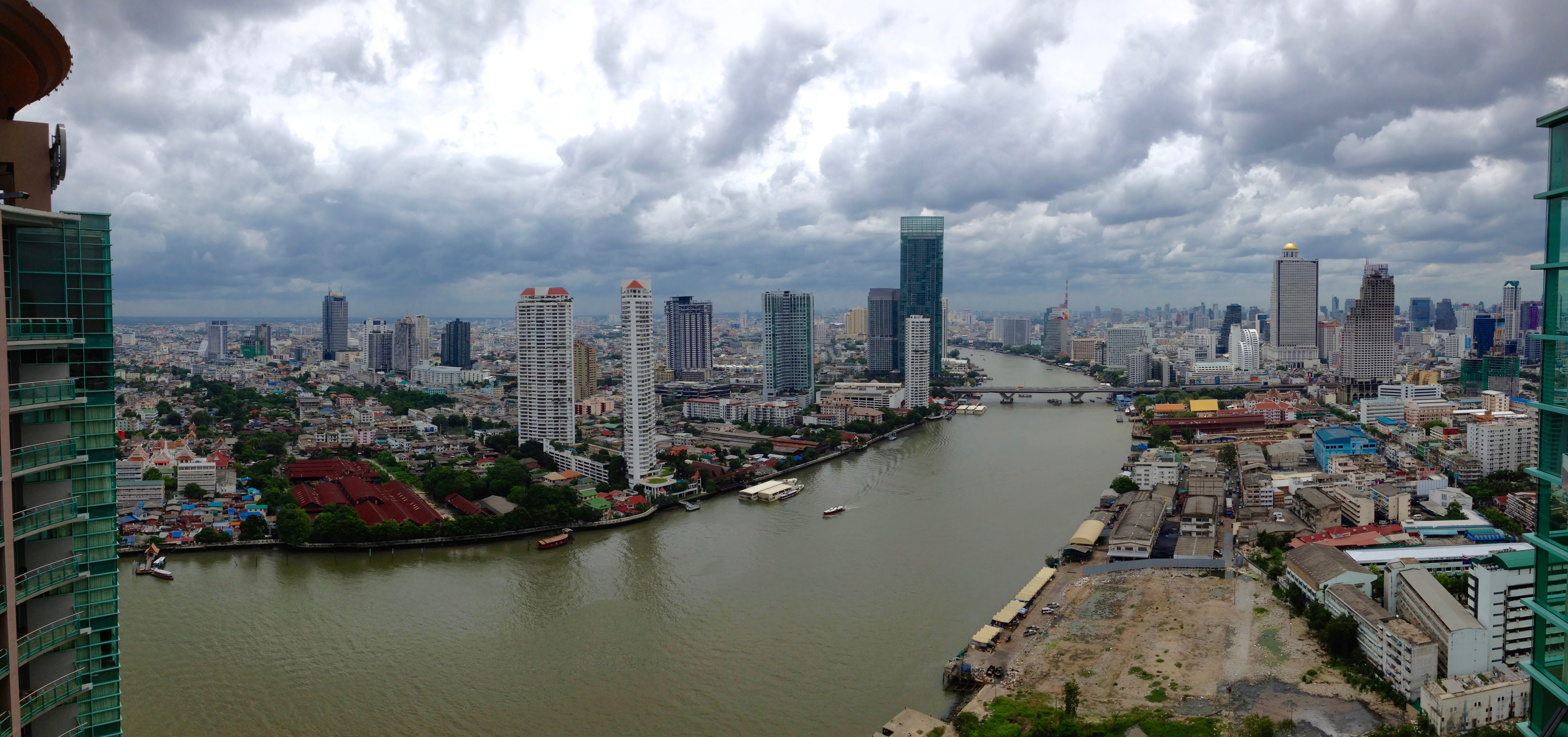 An aerial view of Bangkok showing skyscrapers on both sides of a river.