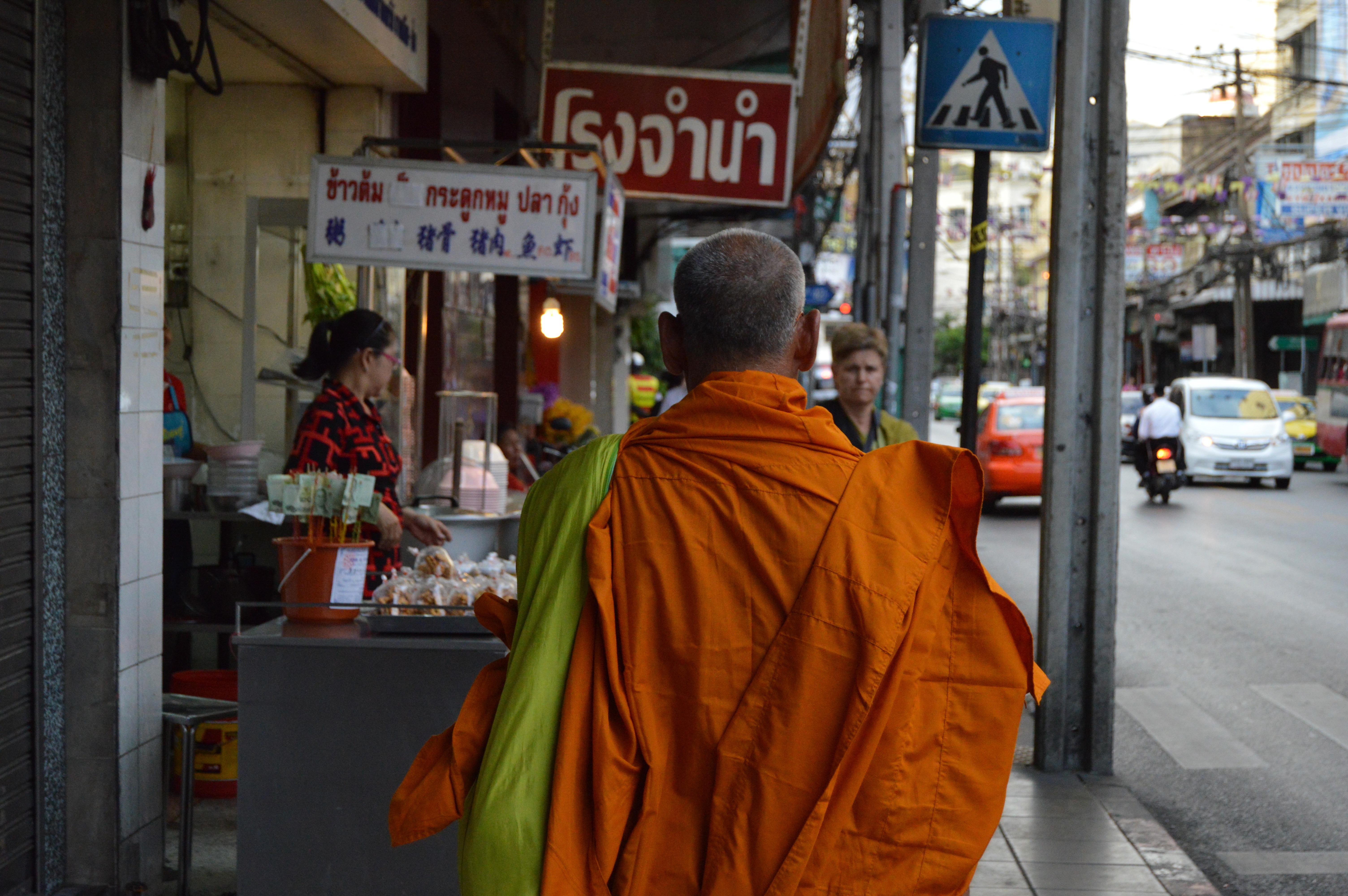 A monk walking down a street in Bangkok.
