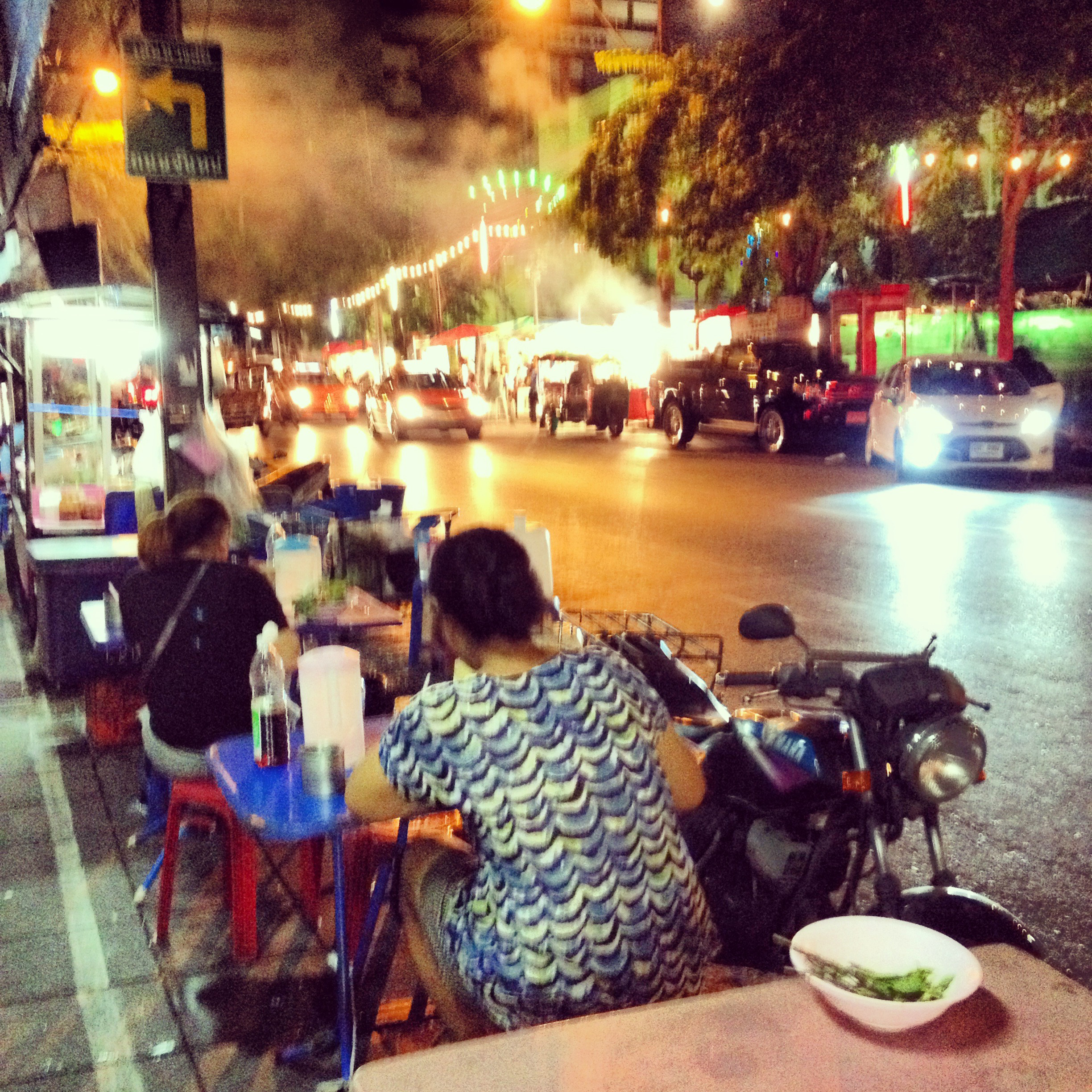 People eating at tables outside on a street in Bangkok.