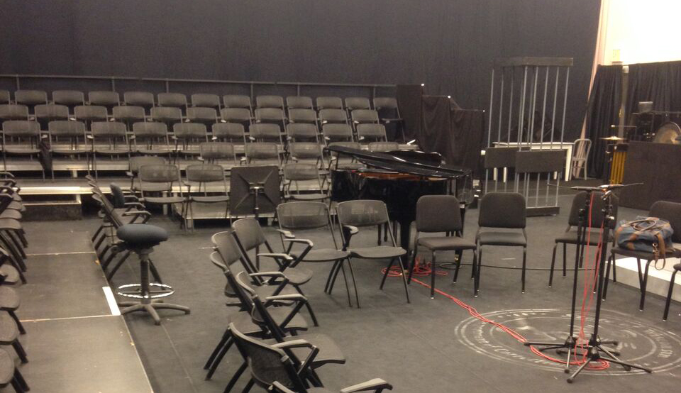 Fold-up chairs and a grand piano set up for the readings inside the black box theater in F. Worth