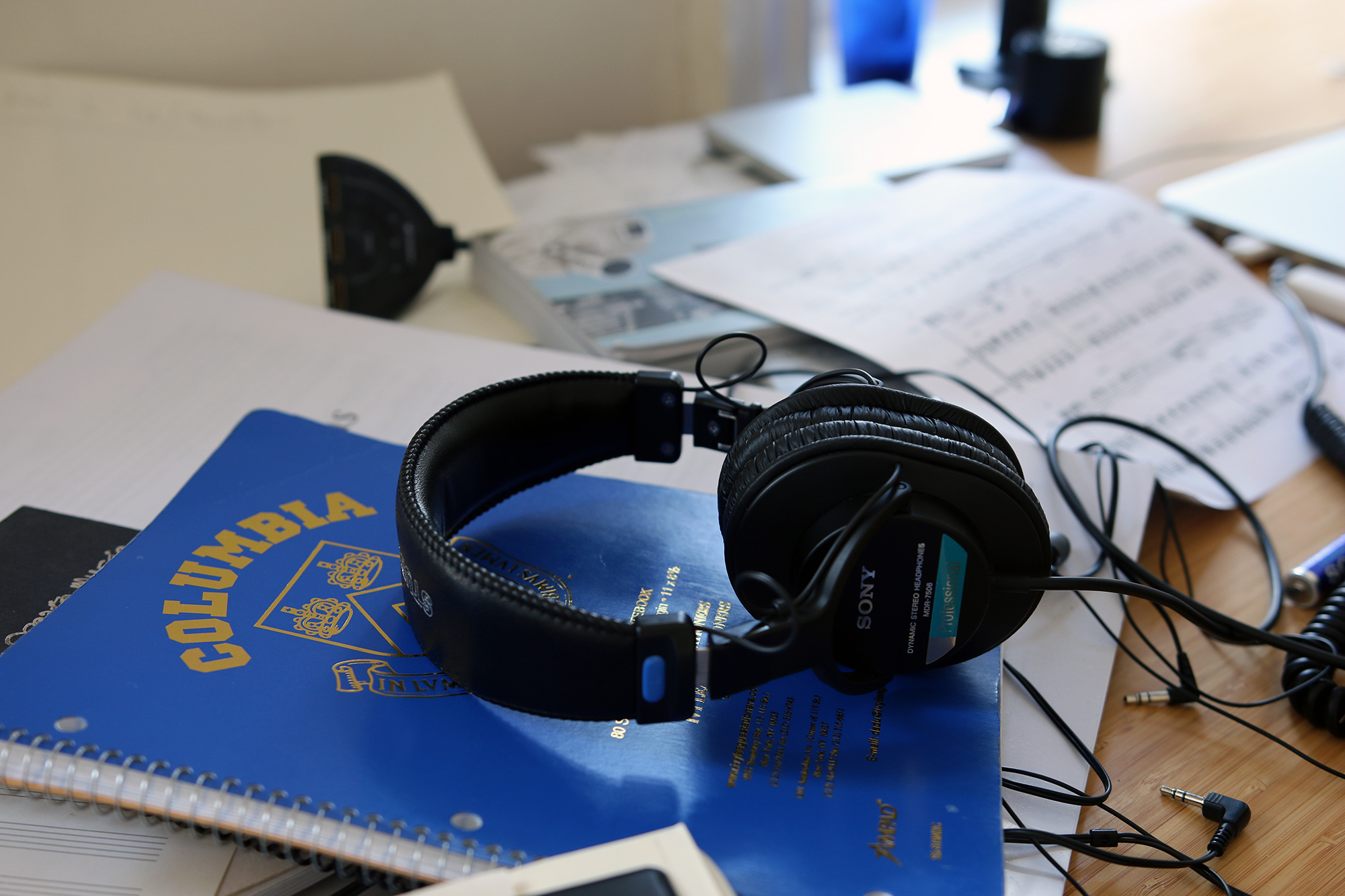 Headphones on top of a Columbia University notebook on Sky Macklay's desk