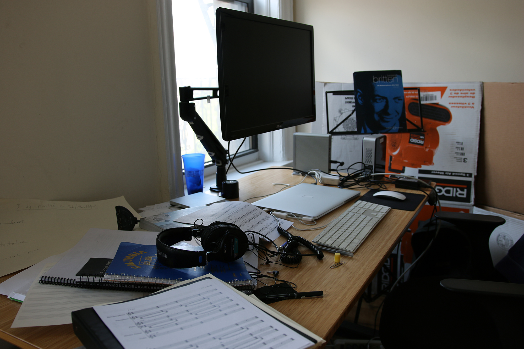 A work table with a closed laptop, an additional computer keyboard and large-scale monitor, headphones, and printed musical scores.