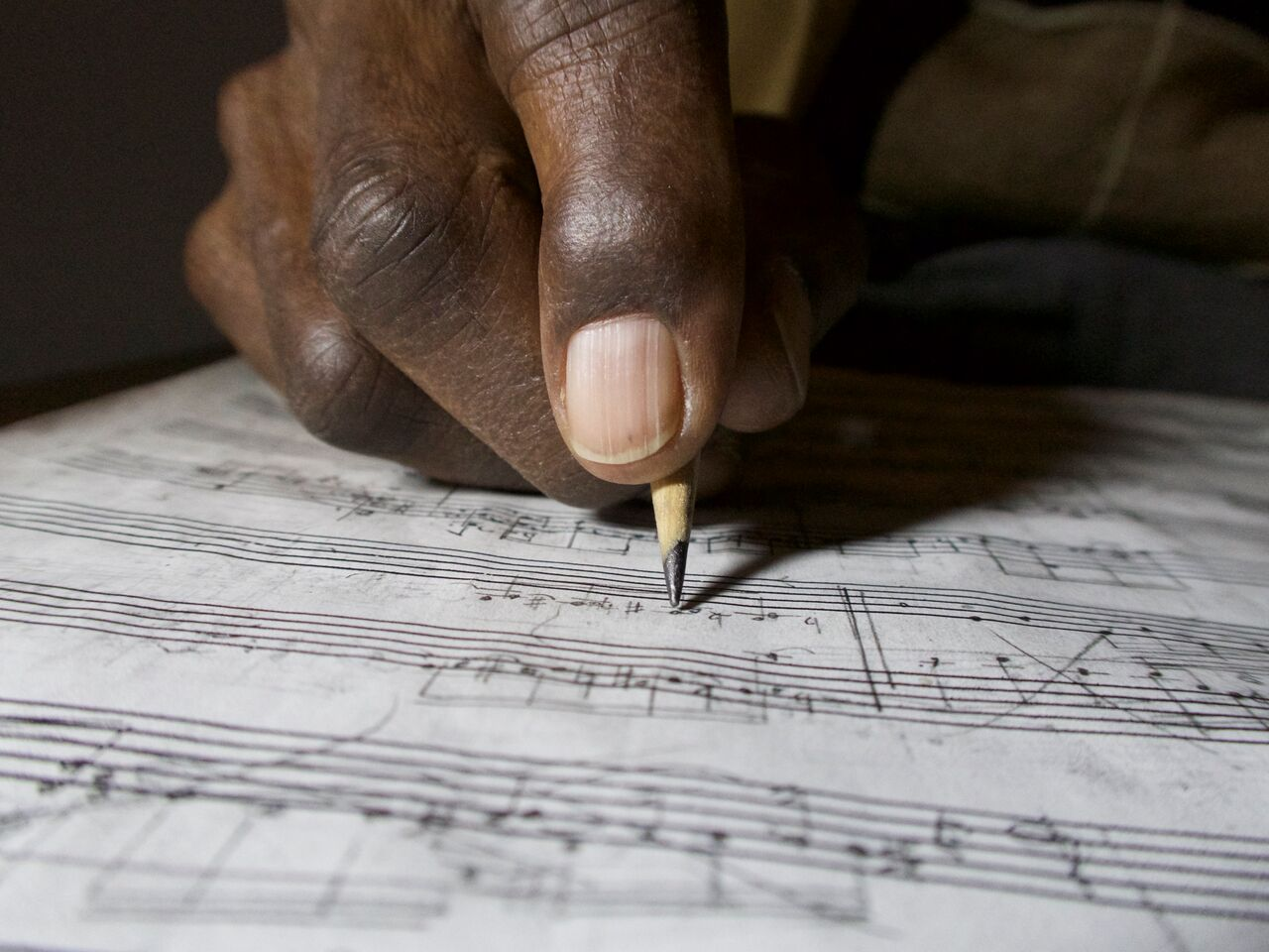 George Walker's hand holding a pencil and writing on a page of music notation paper.
